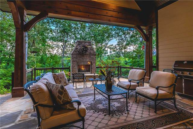 In between the wrought iron sofa and the two cushioned arm chairs is a small rectangular coffee table over a gorgeous patterned area rug with the warmth of the outdoor fireplace just a few feet away. Source: TheHouseDesigners.com