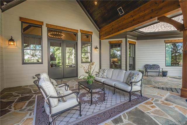 This patio area is right outside the glass doors of the Craftsman-style cottage that is surrounded by tall glass windows and a transom window. Source: TheHouseDesigners.com