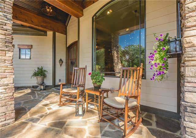 The front porch of the home has a relaxing couple of wooden rocking chairs and a wooden side table perfect for enjoying the morning with a cup of coffee or even as a reading nook. Source: TheHouseDesigners.com