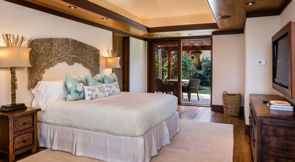 This bedroom suite boasts a luxurious bed set lighted by stylish table lamps and has a widescreen TV on the wall. Images courtesy of Toptenrealestatedeals.com.
