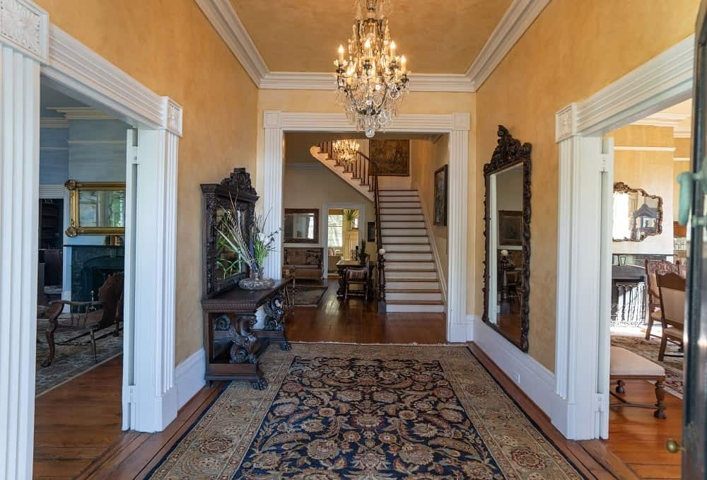 The dramatic foyer has sunny yellow walls with a majestic chandelier in the middle of the ceiling. Images courtesy of Toptenrealestatedeals.com.