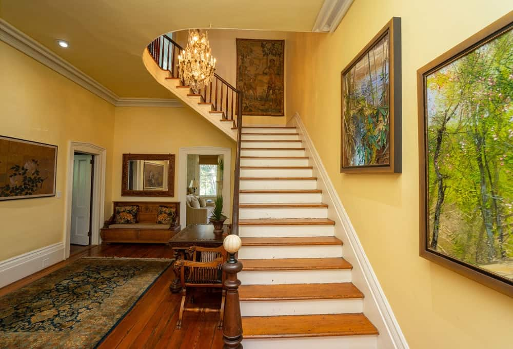 The staircase leading to the second level has wooden steps and decorated with more wall-mounted artworks. Images courtesy of Toptenrealestatedeals.com.