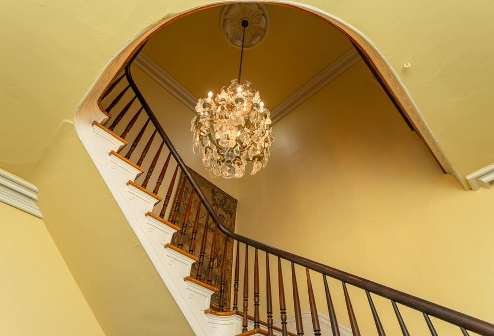 The tall ceiling of the staircase is adorned with a gorgeous chandelier. Images courtesy of Toptenrealestatedeals.com.