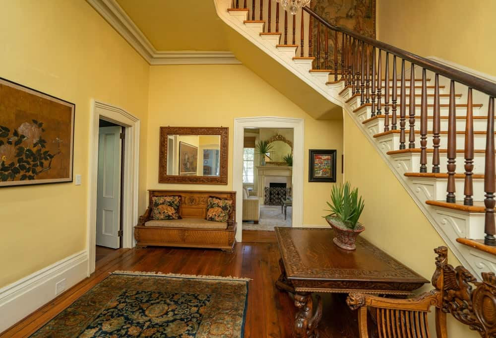 The main hallway has the same sunny yellow walls complemented by the brown wooden furniture. Images courtesy of Toptenrealestatedeals.com.