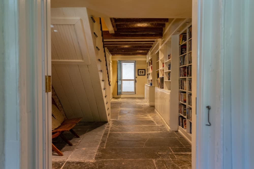 The lower level hallway is lined with built-in bookshelves that set the mood across from the wooden staircase with a reading nook underneath. Images courtesy of Toptenrealestatedeals.com.