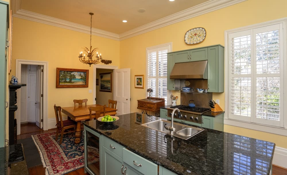 This view of the kitchen reveals the informal dining area beside it that has a rectangular dining table topped with a chandelier. Images courtesy of Toptenrealestatedeals.com.