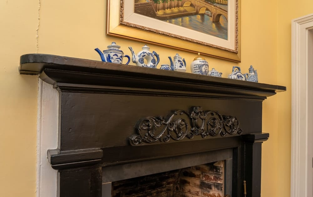 The closer look at the wooden mantle reveals the intricate carvings of the amazing craftsmanship as well as the decorative tea pots above. Images courtesy of Toptenrealestatedeals.com.