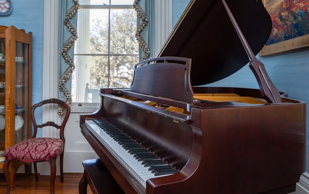 A closer look of the grand piano and its beautiful dark brown hue. to complement the blue curtains of the window. Images courtesy of Toptenrealestatedeals.com.