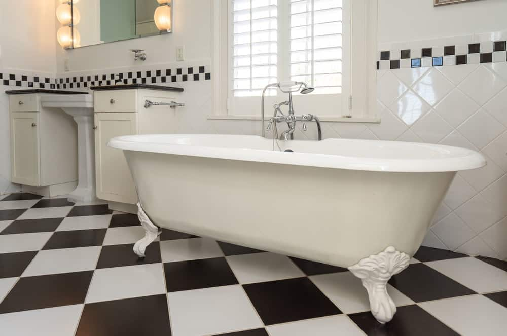 The white freestanding bathtub is placed under a window with white shutters to bring in natural lighting. Images courtesy of Toptenrealestatedeals.com.