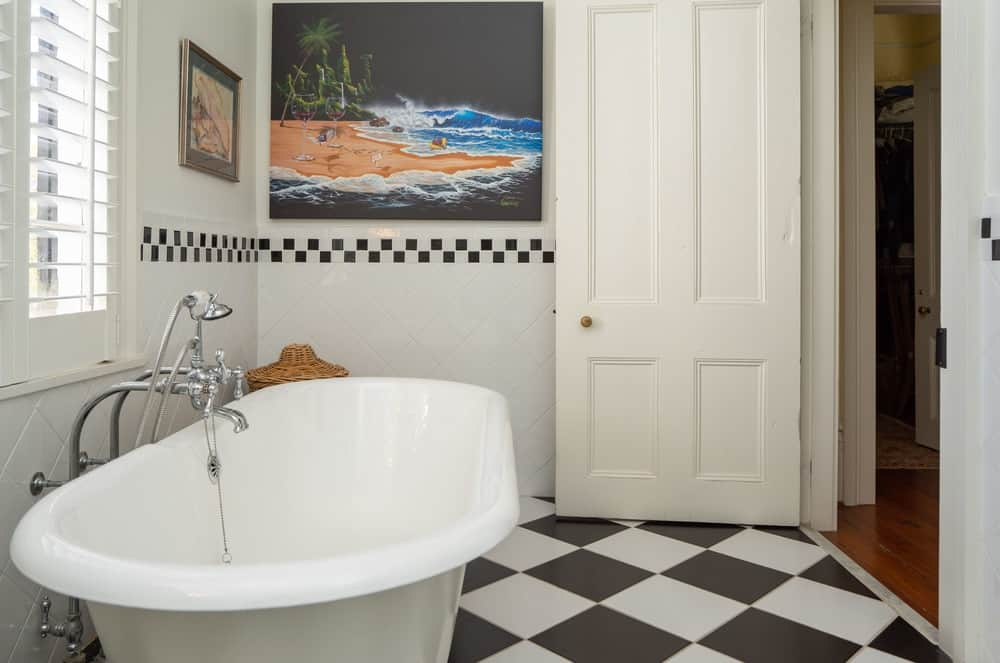 The white door and black and white checkered flooring of the primary bathroom pairs well with the backsplash middle lining. Images courtesy of Toptenrealestatedeals.com.