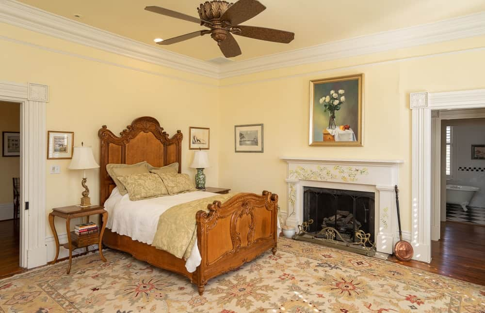 This beautiful bedroom has an antique wooden bed that has a large wooden headboard and a fireplace beside it. Images courtesy of Toptenrealestatedeals.com.