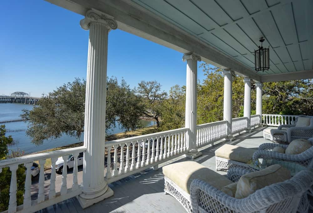 Similar to the porch, this second floor balcony also has several supporting white pillars and comfortable outdoor chairs. Images courtesy of Toptenrealestatedeals.com.