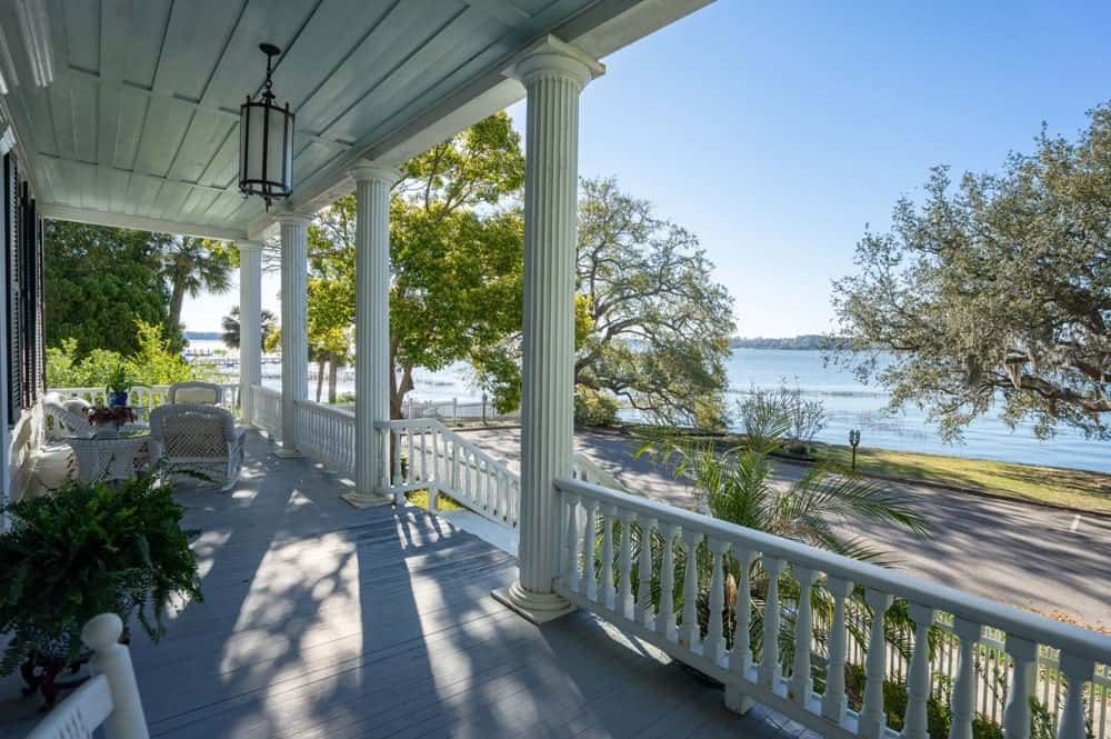 The charming porch has a row of columns supporting the white ceiling with small white railings in between. Images courtesy of Toptenrealestatedeals.com.