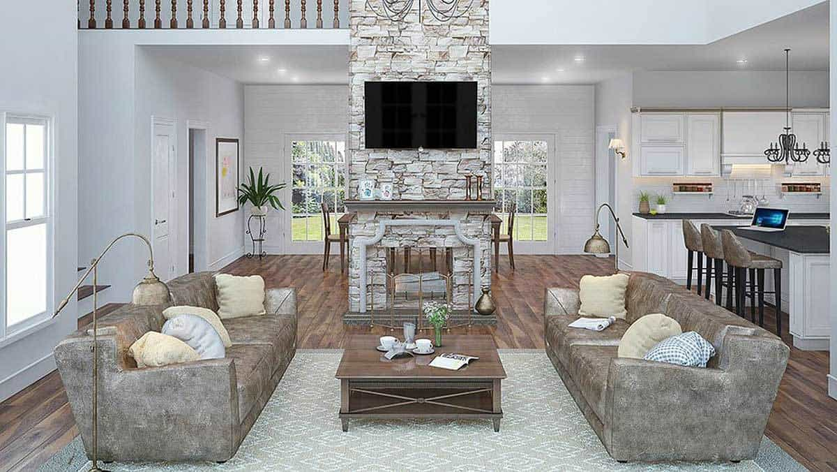 The family room has facing taupe sofas and a wooden coffee table that sits on a patterned area rug. A brick pillar fixed with a TV and a dual fireplace create a sleek focal point.