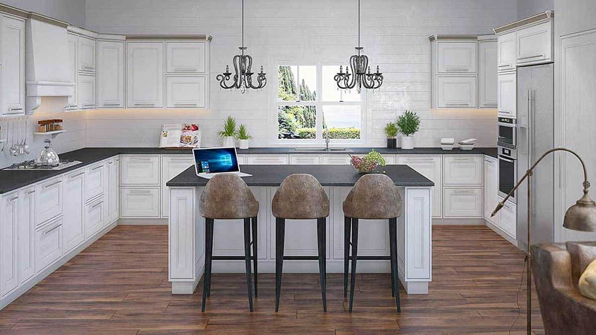 A closer look at the kitchen shows the lovely chandeliers hanging over the breakfast island. Black granite countertops create a stunning contrast to the white cabinets and subway tile backsplash.