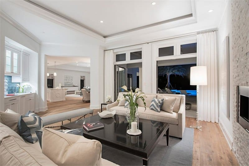 This lovely living room has a view of the kitchen that shares the large room with it on the same hardwood flooring and under the same bright white tray ceiling. The living room has a gray sofa paired with a white square coffee table.