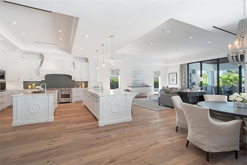 This view shows the great room that houses the living room on the far side beside the kitchen that has the same white tray ceiling. Next to it is an informal dining area with a round wooden dining table surrounded by chairs that has beige slip covers.