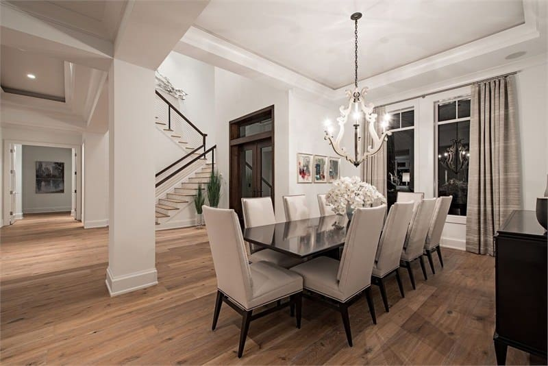 The formal dining room is right beside the foyer that has large dark brown main door with glass panels. The dining room has a long rectangular dark dining table topped with a bright chandelier and surrounded by beige cushioned dining chairs.