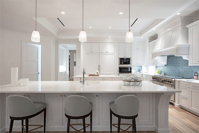 One of the two kitchen islands is paired with three gray cushioned stools for the breakfast bar that is topped with three bright pendant lights.