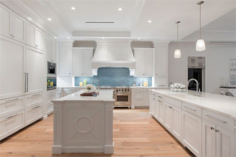 A closer look at the kitchen flaunts of the elegant white shaker cabinets and drawers lining the walls that match perfectly well with the couple of kitchen islands. These matches well with the light hardwood flooring as well as the light gray backsplash.