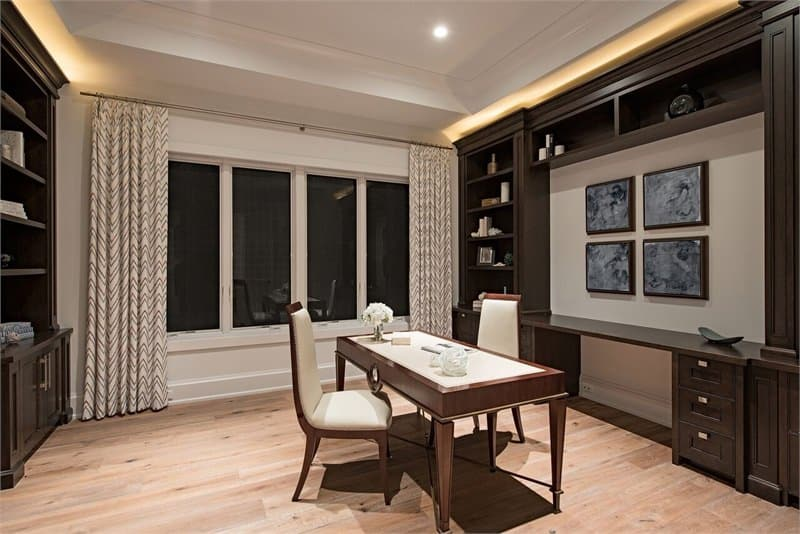 This is a gorgeous home office with an elegant dark brown desk in the middle of the hardwood flooring. This is surrounded by matching brown cabinetry and shelves built into the walls.