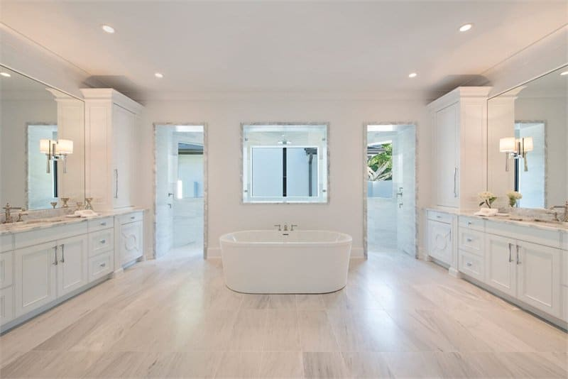 The primary bathroom has a freestanding white porcelain bathtub in the middle of the white marble flooring. On either side of this tub are the two entrances to the shower area next to white wooden vanities topped with large wall-mounted mirrors.