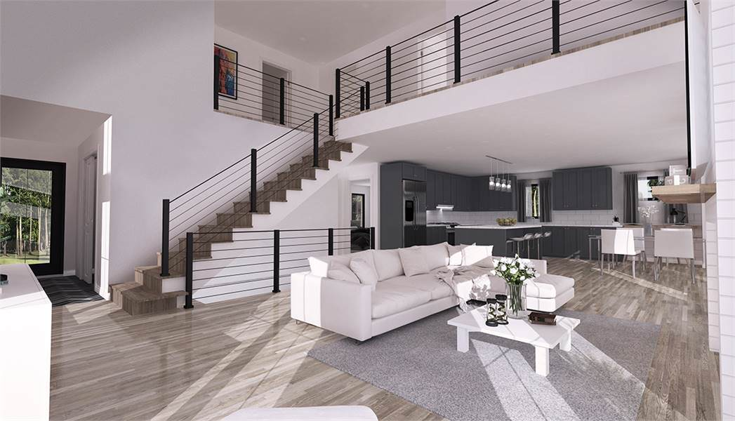 This other angle of the living room shows of the low white coffee table paired with the long sofa. Behind the sofa is the staircase that leads to the upper and lower floors bordered with wrought iron railings for safety.