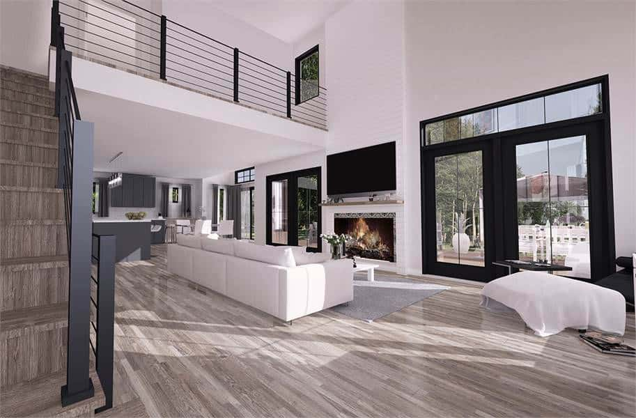 The spacious and airy living room has a tall ceiling paired with an elegant indoor balcony above the long beige sectional sofa that over the hardwood flooring facing the wall-mounted TV above the fireplace.