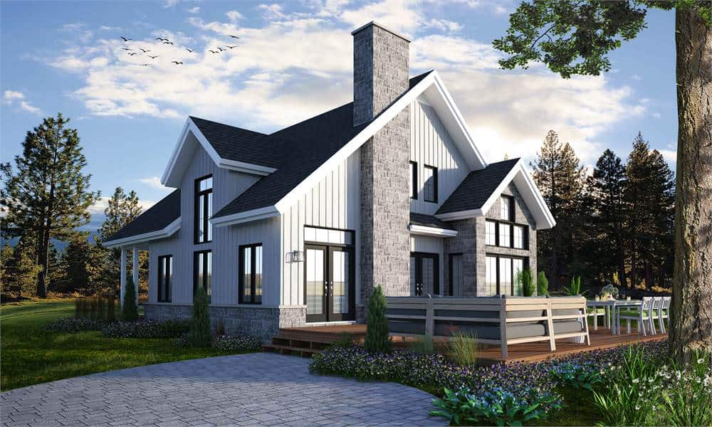 This picturesque Cottage-style home has simple geometric lines and angles giving it an almost unreal beauty. It has a tall gray stone chimney that fits quite well with the dark roofs and the light gray exterior walls. These are then surrounded by beautiful and natural landscaping.