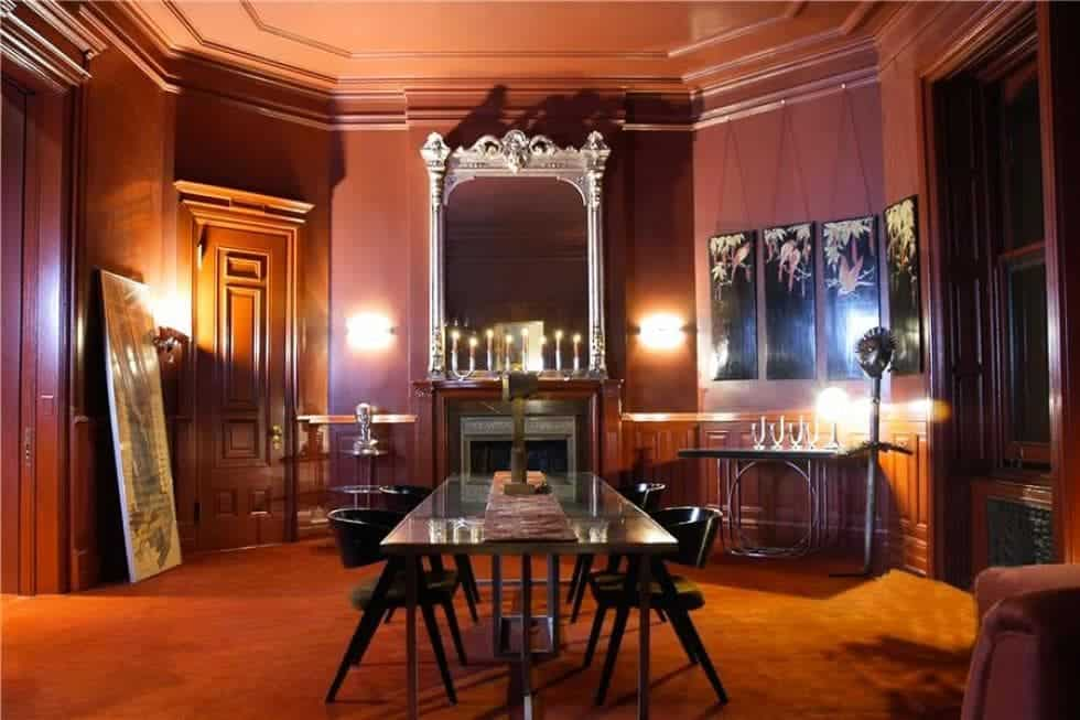 This is the formal dining room with a dark red tone to its walls and the mantle of the fireplace at the head of the glass-top dining table surrounded by black chairs.