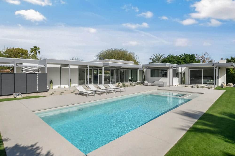 The brilliant blue swimming pool is surrounded by a concrete walkway leading to the glass doors and glass windows of the house. Images courtesy of Toptenrealestatedeals.com.