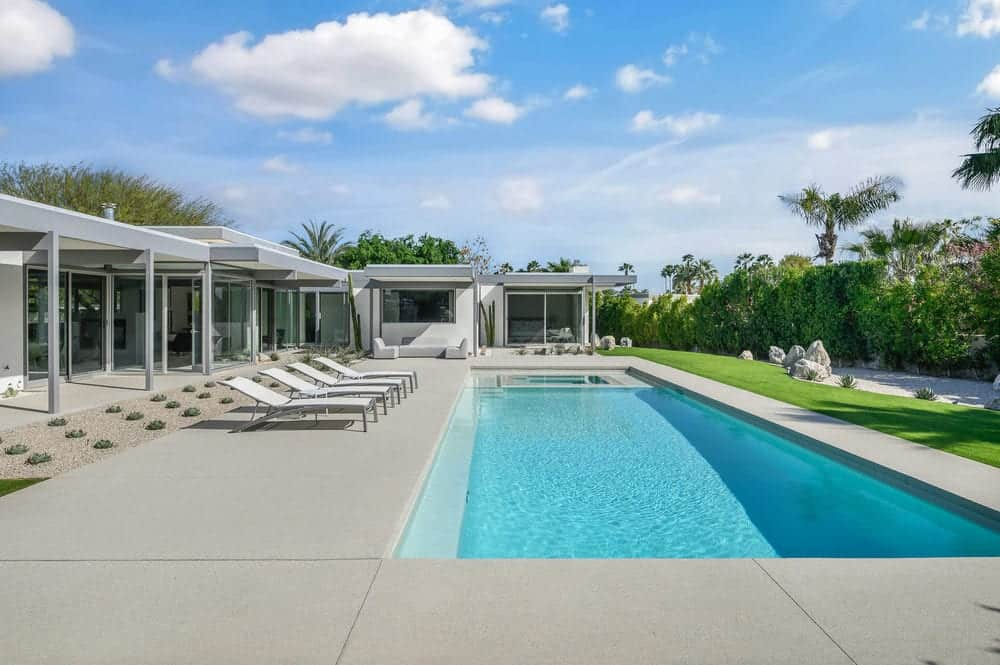 This view of the backyard shows just how big and brilliant the pool is and the luxury that the lawn chairs present to the over-all look along with the tall green privacy walls surrounding the backyard. Images courtesy of Toptenrealestatedeals.com.