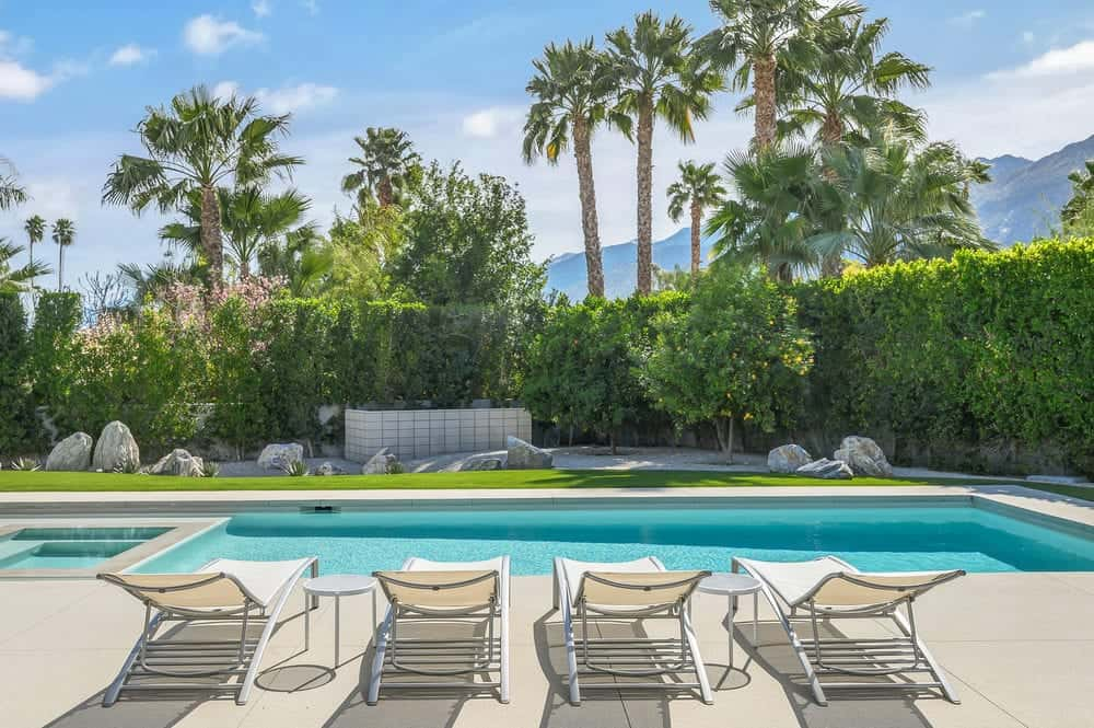 The pool side has concrete walkways that has several folding lawn chairs facing the pool paired with small round tables. Images courtesy of Toptenrealestatedeals.com.