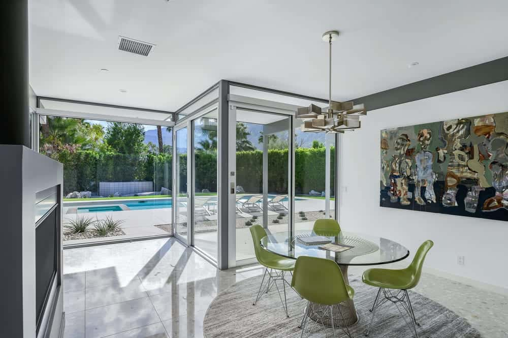 A few steps from the kitchen is the dining area with a round glass-top dining table surrounded by green modern chairs and topped with a decorative chandelier. Images courtesy of Toptenrealestatedeals.com.