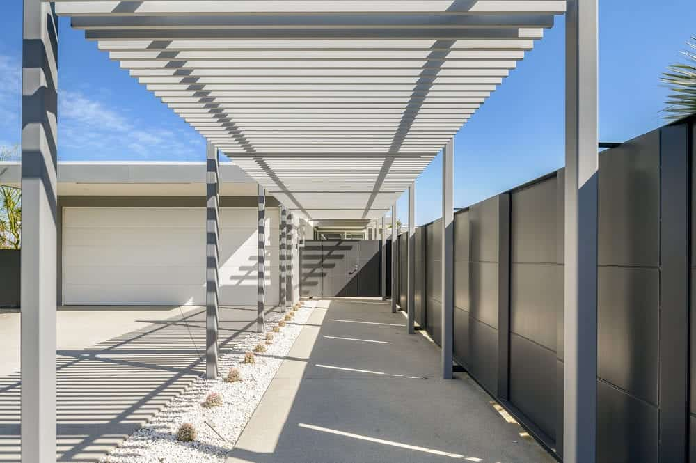 From the spacious front yard that also functions as a parking area, is a lovely walkway with a charming trellis ceiling leading to a gate with the same dark gray tone as the surrounding privacy wall. Images courtesy of Toptenrealestatedeals.com.