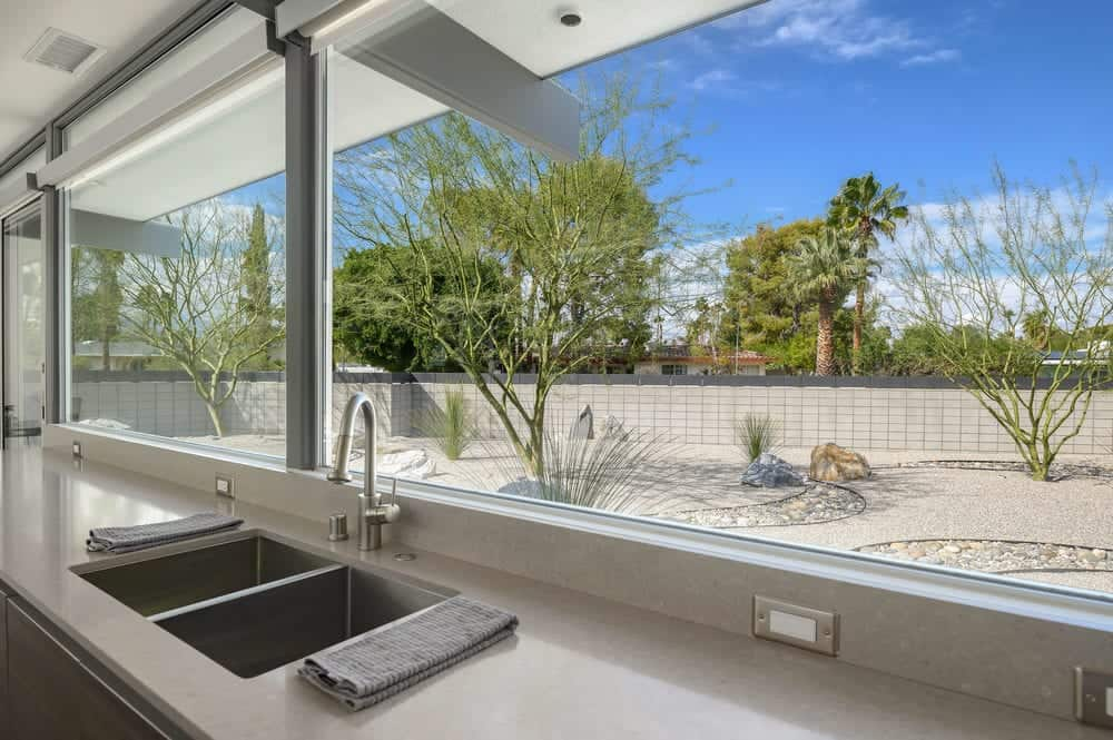 The sink area is topped with a wide glass window that has a beautiful scenic view of the desert landscaping outside. Images courtesy of Toptenrealestatedeals.com.