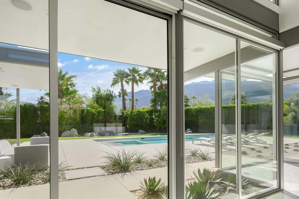 The glass walls of the living room provides an abundance of natural lighting as well as a gorgeous scenic view of the backyard landscape. Images courtesy of Toptenrealestatedeals.com.