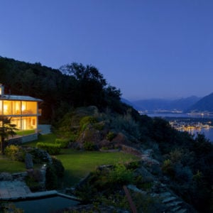 Outside view of the house during night time, warm interior lighting on.