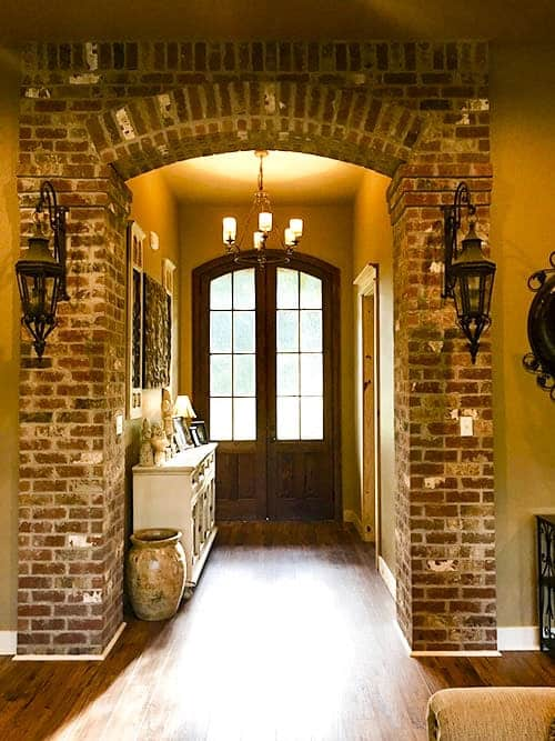 The house foyer with a wooden french door and a brick archway mounted with wrought iron sconces.