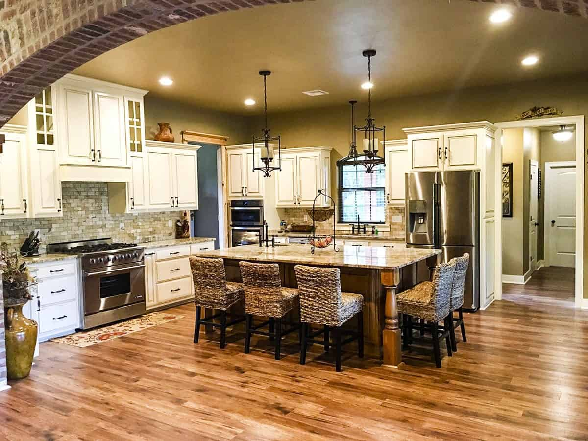 The spacious kitchen with stainless steel appliances and white cabinetry against the brick backsplash.