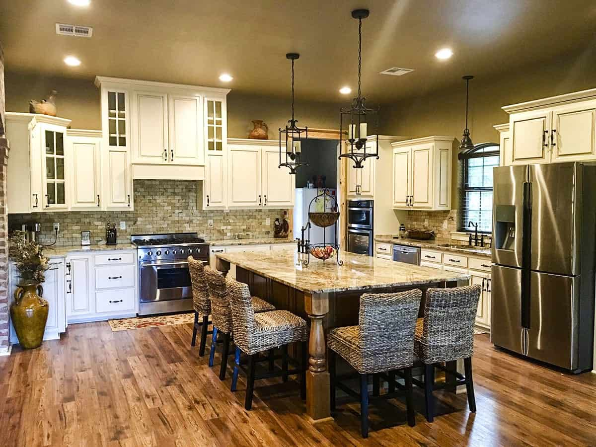 The kitchen features a massive central island paired with wicker counter chairs and caged pendants.