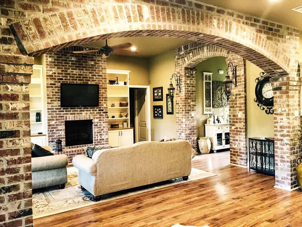 An angled view of the living room shows the large archway behind that's mirrored on the foyer.