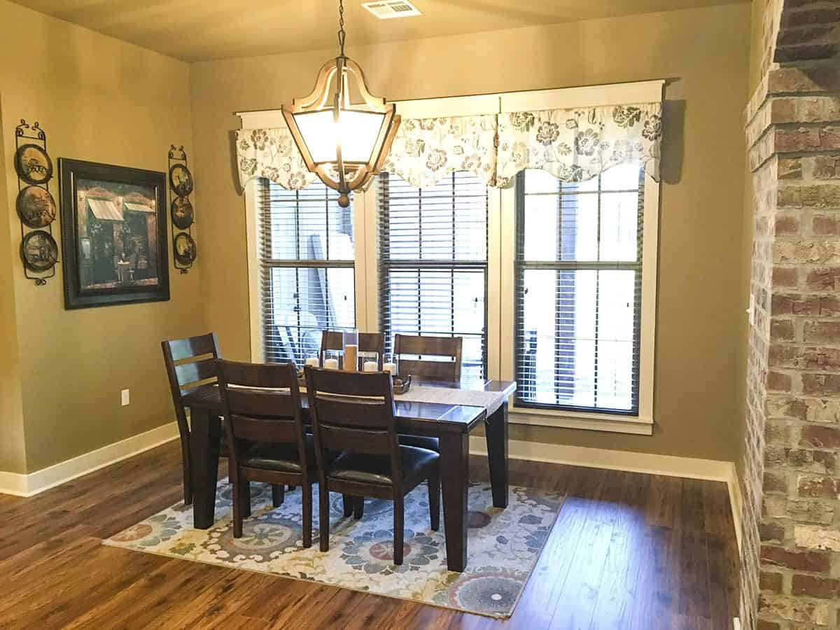 The dining room is flooded with ambient lighting from the large pendant. It is furnished with a dark wood dining set sitting over a floral rug.