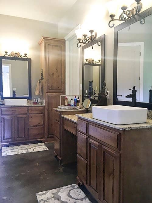 The bathroom has two vanities that are topped wtih vessel sinks. Both are complemented with gray floral rugs and ornate sconces.