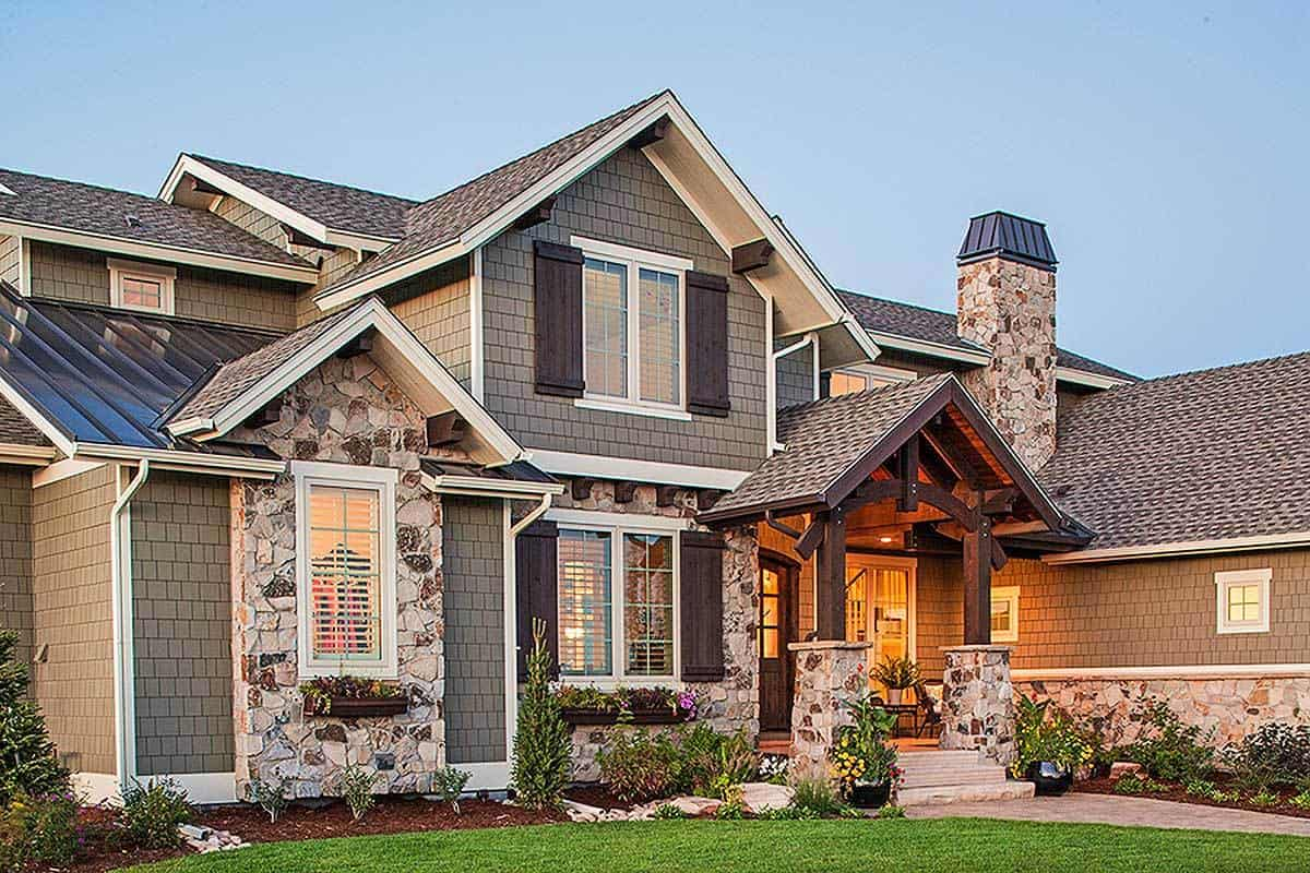The house exterior features gray brick cladding accented with beautiful stone and decorative wood trims.