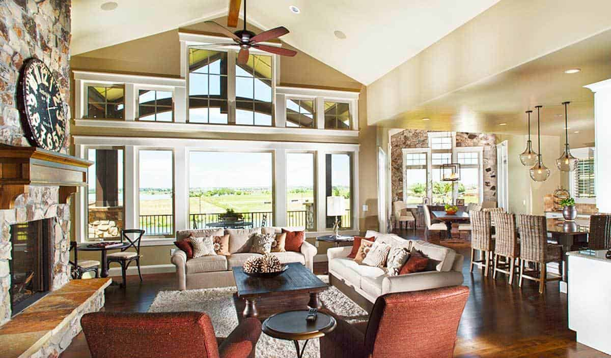 The living area has cozy seats and a rustic coffee table facing the stone fireplace. Large windows overlook an expansive view.