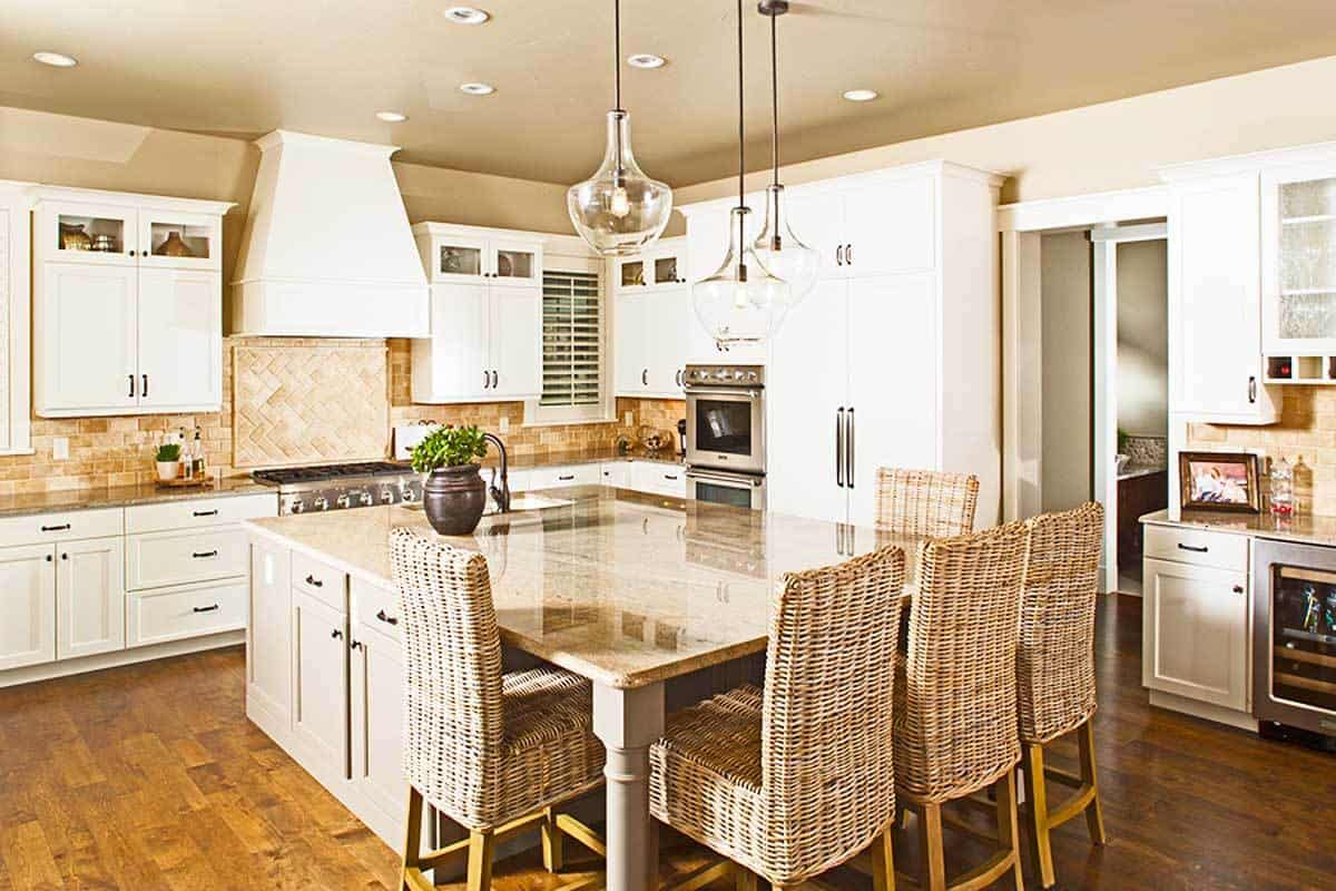 The kitchen showcases white cabinetry and an immense central island paired with wicker counter chairs.