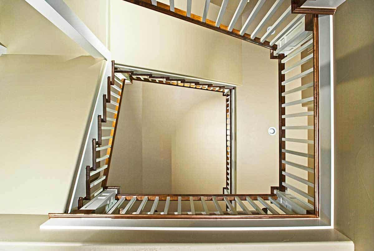View of the staircase with wooden handrails and white spindles from below.