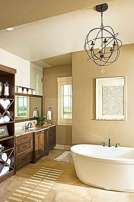 The primary bathroom with natural wood vanity and a freestanding tub under the spherical chandelier.