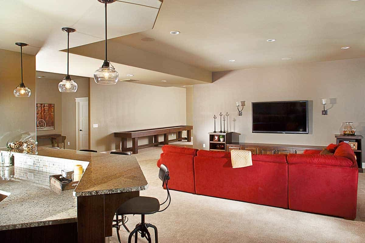 The red sectional sofa stands out against the beige color scheme of this room. A two-tier island bar can be seen on the left side.